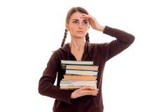 La ragazza astuta stanca dello studente nello sport marrone copre con molti libri della sua posa delle mani isolati su fondo bian Immagine Stock