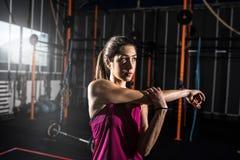 La ragazza atletica fa l'allungamento degli esercizi alla palestra Fotografie Stock Libere da Diritti