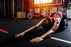 La ragazza atletica fa l'allungamento degli esercizi alla palestra Immagine Stock
