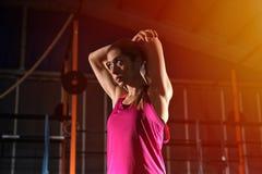 La ragazza atletica fa l'allungamento degli esercizi alla palestra Fotografia Stock Libera da Diritti