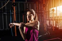La ragazza atletica fa l'allungamento degli esercizi alla palestra Fotografia Stock