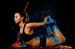 La ragazza atletica giovane ha bagnato in pittura blu ed arancio che fa indietro l'allungamento dell'esercizio Fotografie Stock Libere da Diritti