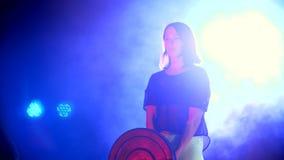 La ragazza atletica, nelle paia sta facendo i vari esercizi di forza con un bilanciere, alla notte, alla luce di multicolore archivi video