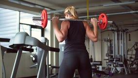 La ragazza atletica occupa con una barra nel primo piano della palestra archivi video