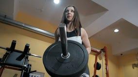 La ragazza atletica risolve alla palestra archivi video