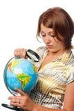 La ragazza attentamente esamina il globo Fotografia Stock