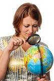 La ragazza attentamente esamina il globo Immagine Stock Libera da Diritti