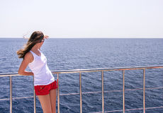 La ragazza attraente è stante e rilassantesi su un yacht Fotografia Stock