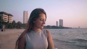 La ragazza attraente in abbigliamento casual posa sul movimento lento della spiaggia archivi video
