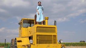 La ragazza attraente balla al rallentatore sulla macchina agricola gialla sul cielo blu del fondo stock footage