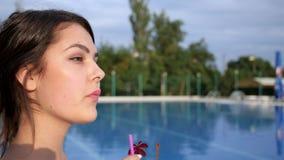 La ragazza attraente beve il cocktail vicino al Poolside sulle vacanze estive stock footage