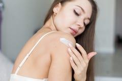 La ragazza attraente in biancheria da letto applica la crema per pelare e la sfrega mentre fa le procedure di mattina moisturizin fotografia stock libera da diritti