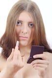 La ragazza attraente con rossetto e lo specchio Immagini Stock