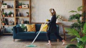 La ragazza attraente in cuffie sta ascoltando musica e ballando con la zazzera durante il lavoro domestico, sta passando lo strac stock footage