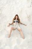La ragazza attraente del brunette si trova sulla sabbia Fotografie Stock Libere da Diritti