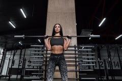 La ragazza attraente e atletica riposa dopo un allenamento duro nella palestra Immagine Stock
