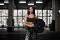 La ragazza attraente e atletica riposa dopo un allenamento duro nella palestra Fotografia Stock Libera da Diritti