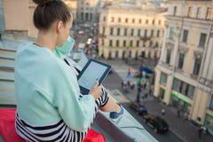 La ragazza attraente ed alla moda si siede sul tetto della casa nella vecchia città e legge il libro elettronico fotografia stock libera da diritti