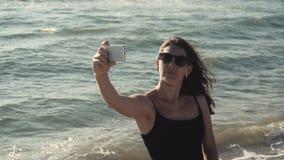 La ragazza attraente fa il selfie sul litorale archivi video