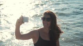 La ragazza attraente fa il selfie sul litorale video d archivio