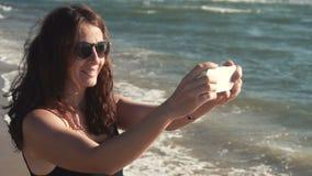 La ragazza attraente fa il selfie sul litorale stock footage
