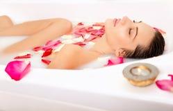 La ragazza attraente gode di un bagno con latte Fotografia Stock