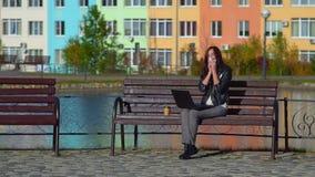 La ragazza attraente nel parco su un banco con un computer portatile, starnutisce, pulisce il suo naso con un fazzoletto stock footage