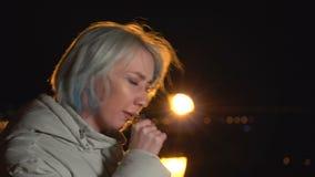 La ragazza attraente in rivestimento bianco dello schermo sta tossendo Città di notte sui precedenti video d archivio