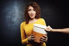 La ragazza attraente sembra lo sforzo triste per il secchio del popcorn con l'amico Fotografia Stock