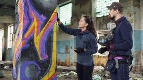 La ragazza attraente sta imparando come creare i graffiti nell'ambito di orientamento del tipo barbuto bello dell'artista profess archivi video