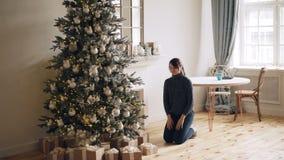 La ragazza attraente sta portando i contenitori di regalo all'albero di Natale, sta mettendoli sotto l'abete e sta sorridendo poi video d archivio
