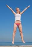 La ragazza attraente sta saltando sorridere Fotografia Stock