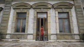 La ragazza attraente in vestito rosso va sul balcone di vecchia proprietà terriera video d archivio