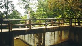 La ragazza attraversa il fiume nella giungla stock footage