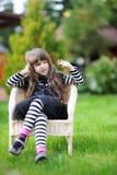 La ragazza in attrezzatura di Halloween mostra nel giardino Fotografia Stock