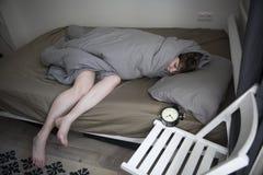La ragazza, avvolta in una coperta grigia, mette fuori la sua mano per spegnere l'allarme Ci sono sei ore sulla sveglia immagini stock libere da diritti