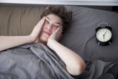 La ragazza, avvolta in una coperta grigia, mette fuori la sua mano per spegnere l'allarme Ci sono sei ore sulla sveglia immagine stock libera da diritti