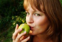 La ragazza bacia la mela Immagine Stock