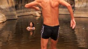 la ragazza bagna il tipo entra in lago caldo creato tramite la torrente montano stock footage