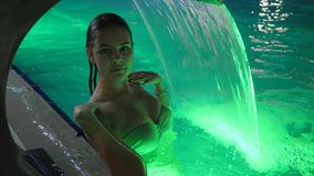 La ragazza bagna sotto la cascata artificiale in Poolside a resto dell'estate alla località di soggiorno nella notte archivi video