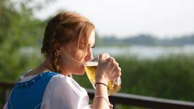 La ragazza bavarese beve il vetro della vista della parte posteriore della birra archivi video