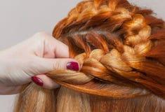 La ragazza bella con capelli rossi, parrucchiere tesse un primo piano della treccia, in un salone di bellezza immagini stock