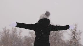 La ragazza bella prende i fiocchi di neve, nel parco dell'inverno sul Natale weekend ragazza felice che gioca nella foresta in fo stock footage