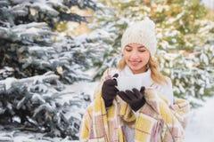 La ragazza beve all'aperto nella foresta dell'inverno Fotografia Stock