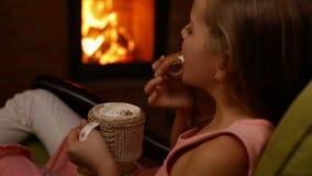 La ragazza beve la cioccolata calda e mangia il biscotto a forma di cuore stock footage
