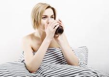 La ragazza beve il caffè a letto Ragazza che di mattina la ragazza sveglia di mattina sonno Mattina che si sveglia Leggendo la st Fotografie Stock Libere da Diritti