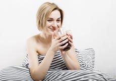 La ragazza beve il caffè a letto Ragazza che di mattina la ragazza sveglia di mattina sonno Mattina che si sveglia Leggendo la st Immagine Stock
