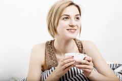 La ragazza beve il caffè a letto Ragazza che di mattina la ragazza sveglia di mattina sonno Mattina che si sveglia Leggendo la st Fotografia Stock
