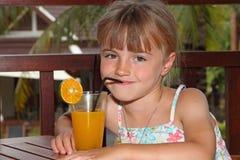 La ragazza beve il succo di arancia Fotografia Stock Libera da Diritti