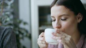 La ragazza beve il tè caldo in un caffè stock footage